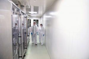 Gruppe Arbeiter in Schutzkleidung im Reinraum in der Pharmaindus