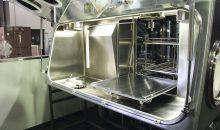 1: Reinigungsanlage mit vorgesetztem Isolator. Der Waschgutträger ist auf in der Tür integrierten Schienen für die Beladung positioniert.  (Bilder: Belimed)