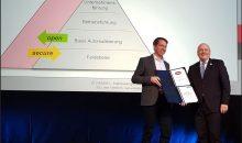 Namur Vorstandschef, Dr. Felix Hanisch, und Arne Schönbohm, Präsident des BSI, tauschen die Urkunden zum Namur-Beitritt zur Allianz für Cyber-Sicherheit und zum BSI-Beitritt zur Namur aus. Bild: Redaktion