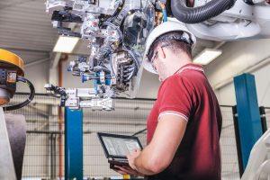 3_Techniker überprüft Roboter mit Laptop