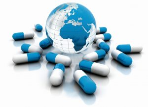 Medicine pills and world globe isolated on white