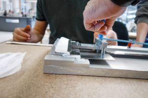 Die maschinell hergestellten Stoff-Zuschnitte werden in die Vorrichtung eingelegt und mit nur einem Handgriff gefaltet. (Bild: Optima/Wrapping Solutions)