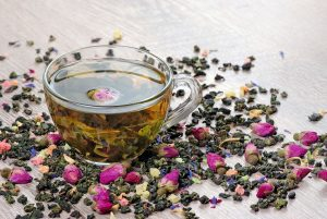 green tea. cup of green tea with flowers and fruit pieces. blend