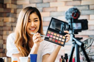Charming Asian girl recording vlog. Beauty blogger presenting makeup cosmetics in front of camera