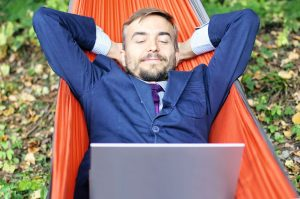 Happy businessman with laptop relaxs in a hammock on nature. Fre
