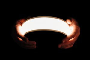 Flexible lighting oled panels in male hands on a black backgroun